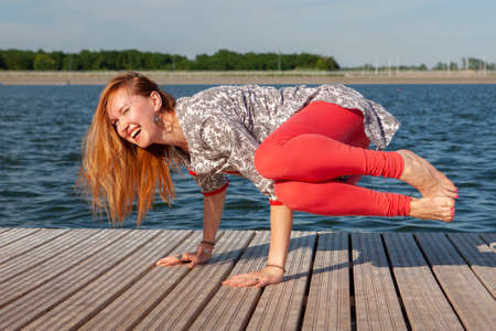 An image of a pretty woman doing yoga at the lake. Portrait Stock Photo