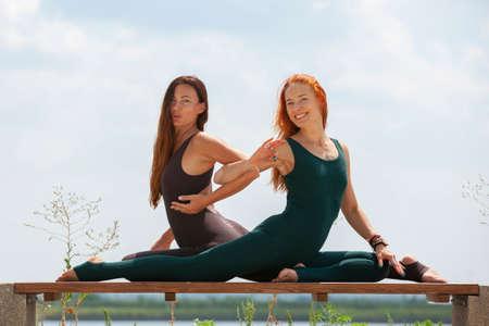 Due belle donne che si allungano in un parco prima di iniziare una sessione di allenamento - Ragazze che fanno esercizi di ginnastica all'aperto. Ritratto