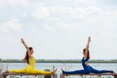 Two happy smiling blond girls doing yoga exercise together in morning in beautiful mountain lake landscape. Yoga retreat, sport outdoor. Portrait 免版税图像
