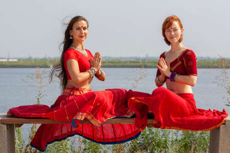 Pair of girls practice yoga. Women in a traditional saree. Portrait.