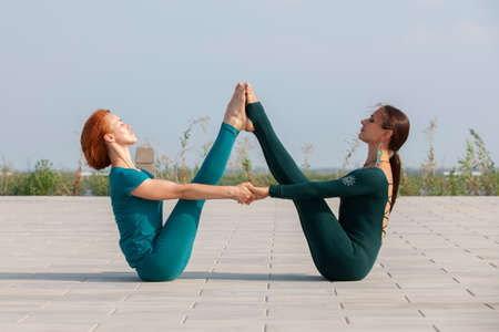 Beautiful women exercizing yoga together on the nature. Concept of relationship, love, summer, weekend, honeymoon, healthy lifestyle. Portrait.