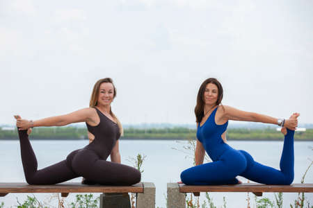 Two happy smiling blond girls doing yoga exercise together in morning in beautiful mountain lake landscape. Yoga retreat, sport outdoor. Portrait