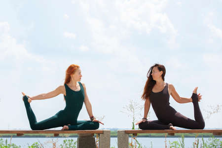 Two pretty women stretching in a park before starting a workout session - Girls doing gymnastics exercises outdoors. Portrait