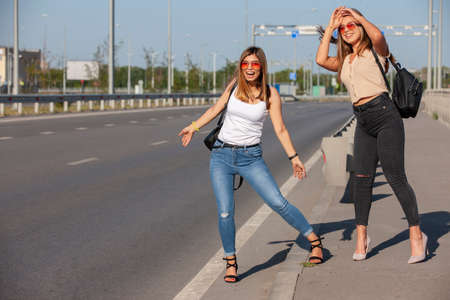 Two beautiful young women are hitchhiking on the road and try to find someone to take them to their hotel. Portrait.