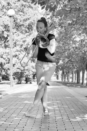 Girl learning to play trombone. Girl plays standing on the alley of a city park. Portrait.