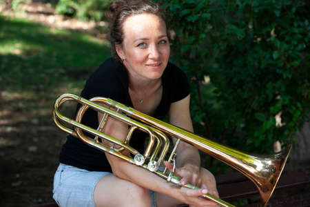 Girl learning to play trombone. Portrait of a girl on a background of a city park park. Portrait. Close-up. Фото со стока