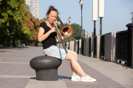 Girl learning to play trombone. Girl plays sitting on the promenade. Portrait.