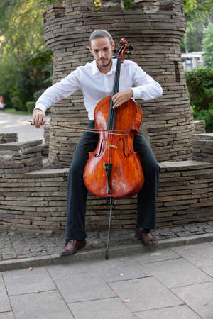 Young man playing cello outside. Cellist playing classical music on cello. Portrait