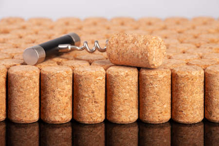 Corkscrew and wine cork as background. Limited depth of field. Close-up.