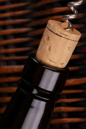 Opening a wine bottle with a cork screw in a restaurant. Against the background of a wicker basket of vines. Limited depth of field. Close-up