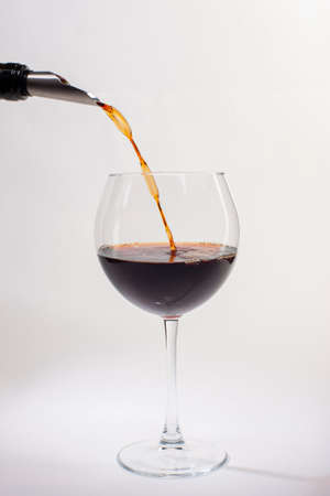 Pouring red wine into the glass. Glass of red wine on a white background and with soft shadow. Close-up.