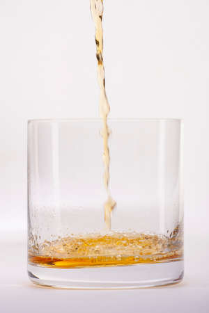 Close-up of an elegant glass for spirits, with a spilled liquor, similar to rum or whiskey, on a white background. Limited depth of field.