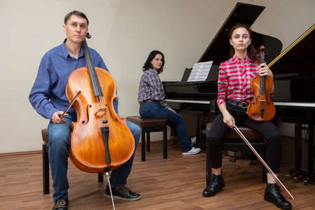 Family trio rehearsing. Father plays the cello, daughter is a violinist, mother plays the piano. Portrait. Stockfoto