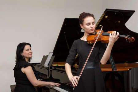Musicians of the symphony orchestra. Young violinist and pianist in concert dresses. Portrait.