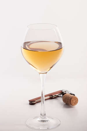 View with shallow depth of field of a glass of white wine with a sommelier tools. Close-up. Banco de Imagens