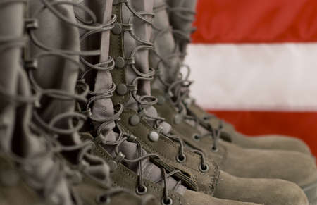 Sage green military combat boots with US flag in the background.
