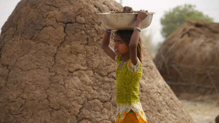 GWALIOR, INDIA - APRIL 17, 2016: An unidentified indian village girl carrying cow dung over her head.