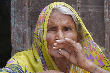 GWALIOR, INDIA - APRIL 15, 2016: An unidentified indian old women sitting and smoking. Editorial