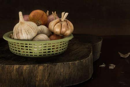 garlics: garlics and onions on wooden cutting board.