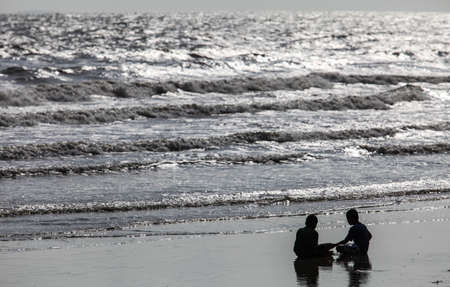 silhouette of kids playing on the beach photo