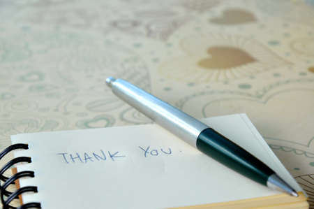 Say thank you with a text message on paper and pen photo