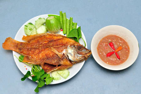 Pan fried fish , chili sauce , vegetable photo