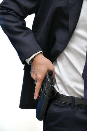 firearms: Agent wearing white shirt drawing gun from holster Stock Photo