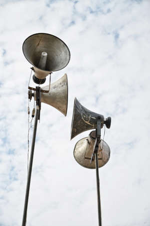 Chromed loudspeakers with sky background and sound wave effect photo
