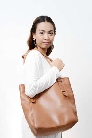 inocent: Young woman with leather bag on white background