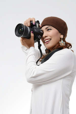 Young woman holding and looking into a camera photo