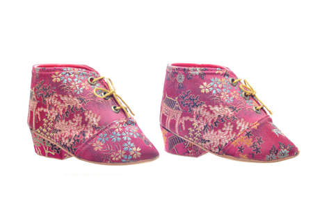 Miniature antique chinese womans shoes worn by an old woman with bound feet Stock Photo