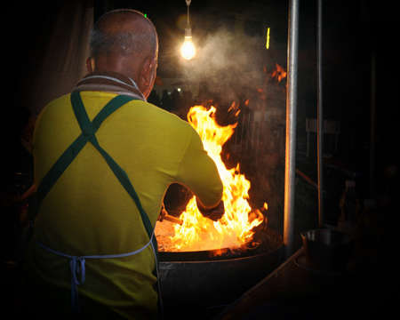 Chef cook making a show with flames while cooking in a night market.