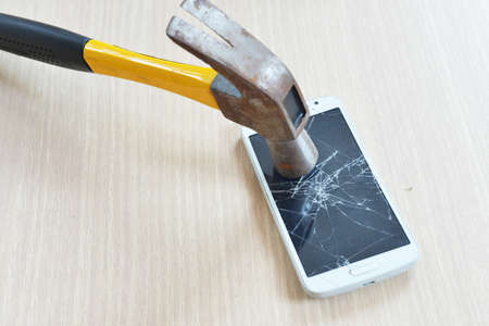 Close up of crash mobile phone smash by rusty iron hammer on wooden table. Stock Photo