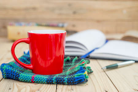Red cup of coffee and books opened diary on wooden table.