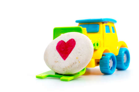 Toy plastic forklift hold heart stone , Love and Valentine day concept. Stock Photo