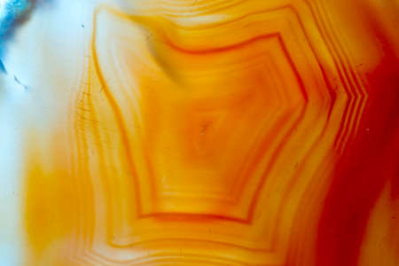 Close up of natural orange agate crystal surface, orange agate crystal cross section. abstract background texture.