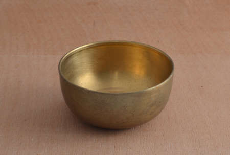 Ancient brass bowl for special ceremony on wooden table.