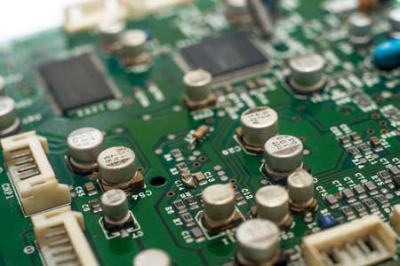 close-up circuit board with electronic components on green printed