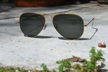 Gold frame aviator black sunglasses on floor Reklamní fotografie
