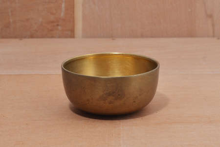 Ancient brass bowl for special ceremony on wooden table. alloy bowl rubbed with stone ,handmade product of thailand Reklamní fotografie