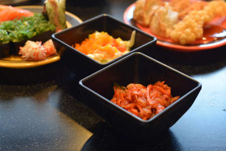 Spicy kimchi salad and Sushi, Asian food assortment.
