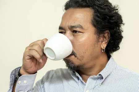 Man drinking coffee in a mug, with serious face