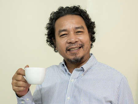 Man drinking coffee in a mug, Smiling and happy