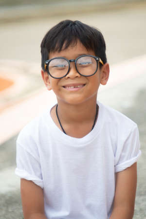 Asian boy wearing a white T-shirt with glasses, sitting, smiling happily Reklamní fotografie - 128178043