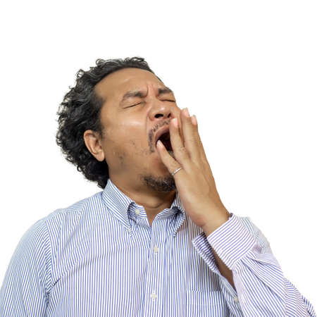 Tired business man yawning isolated on a white background. Stock Photo