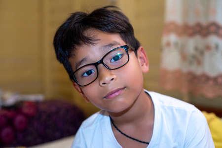 Asian boy wearing a white T-shirt with glasses happy. 版權商用圖片