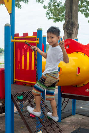 Portrait of cute Asia boy smiling happily playing on the color playground 版權商用圖片