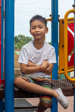 Portrait of cute Asia boy smiling happily playing on the color playground Stock Photo
