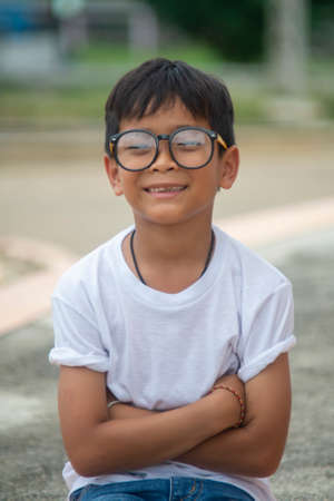 Asian boy wearing a white T-shirt with glasses, sitting, smiling happily 版權商用圖片
