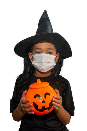 The boys wearing protective mask holding a halloween pumpkin and wearing a witch hat halloween.
